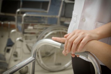 Doctor holding patient 's hand in a walker