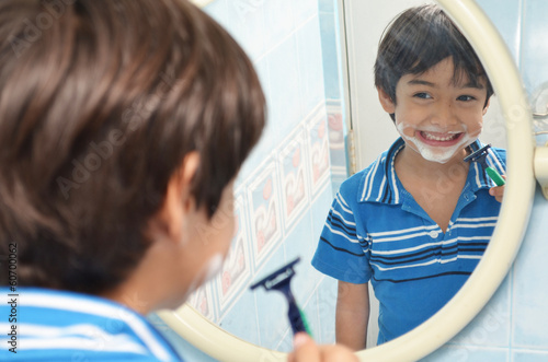 Little boy pretending to shave in the mirror