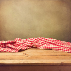 Empty wooden deck table with tablecloth over grunge background