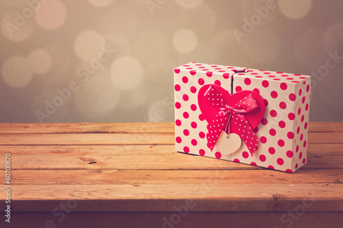 Gift box with heart shape on wooden table