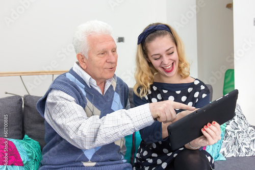 Grandfather and granddaughter with tablet