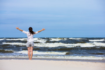 Teenage girl standing on beach, arms up