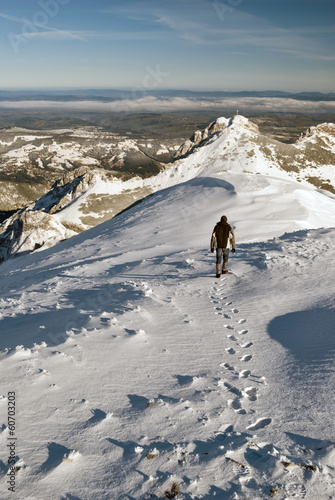 Tourist hiking near Giewont in winter, Tatra Mountains, Poland