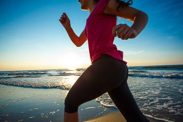 Teenage girl running, jumping on beach