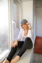 Woman on windowsill smile and touch hat