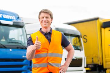 Spediteur vor Lastwagen und LKW auf Depot