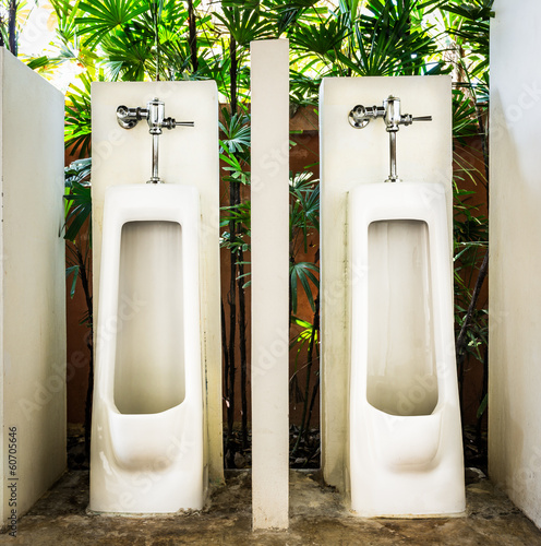 restroom interior design with white urinal row