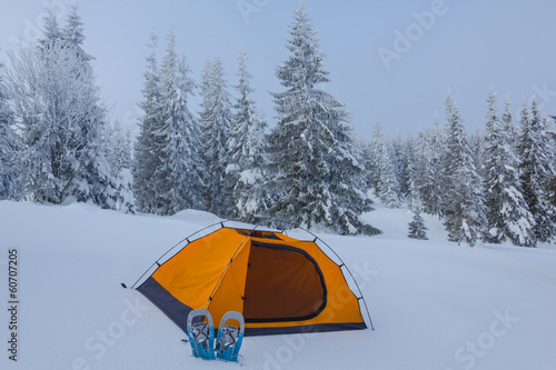 orange touristic tent in a winter forest