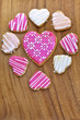 Iced heart shaped cookies on wooden board.