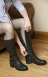 Woman zipping up a pair of black leather boots