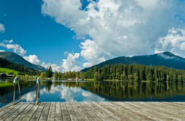 Wharf by the Schwarzsee in Austria with mirror reflection