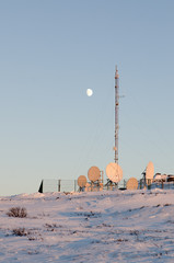 Moon above the arctic cell site illuminated by the setting sun