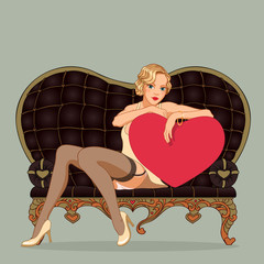 Vintage pin-up girl sitting on the black leather sofa