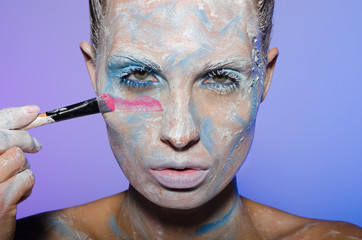 Woman paints her face with colors