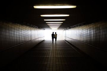 Couple in silhouette walking towards pedestrian underpass exit
