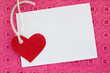 A blank white note card on pink background
