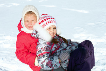two girls sledding in winter
