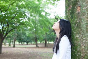 木に寄りかかる女性