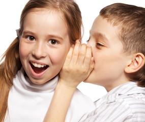Boy whispers girl in the ear secret