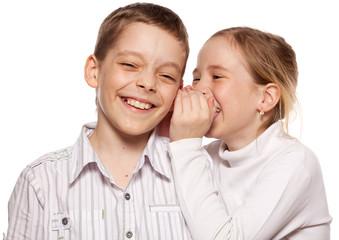 Girl whispers boy in the ear secret
