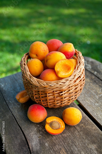 apricots in a basket on wooden background