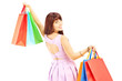 Attractive female in dress holding shopping bags