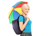 Blond female student walking with umbrella and looking at camera