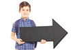 Boy with school bag holding a big black arrow pointing right