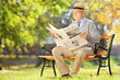 Senior gentleman sitting on a bench and reading a newspaper