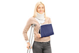 Happy blond female with broken arm holding a crutch