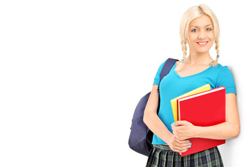 Female student with school bag holding books