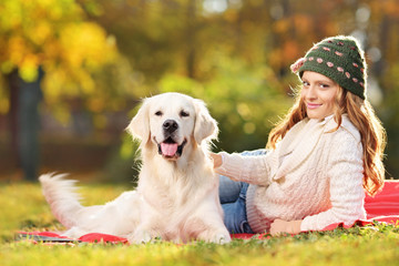 Pretty female lying down with a dog in a park