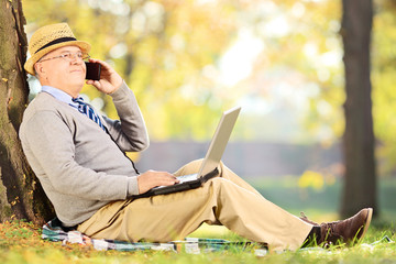 Senior man in park, talking on a phone and holding laptop