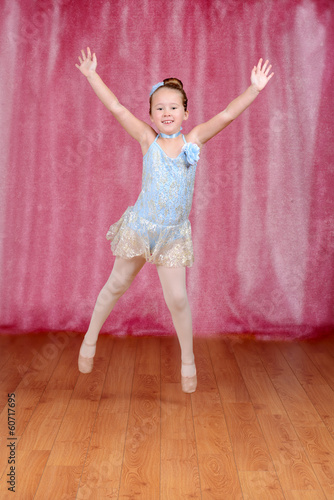 Little ballerina jumping in blue tutu