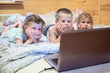 Pretty children looking at computer monitor while laying in bed