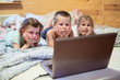 Three children looking at laptop monitor while laying in bed
