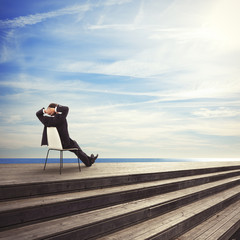 young businessman sitting on a chair looks the sea