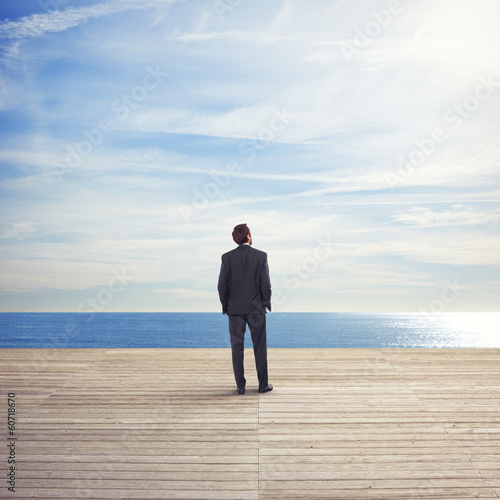 Business man standing on a pier looks the sea