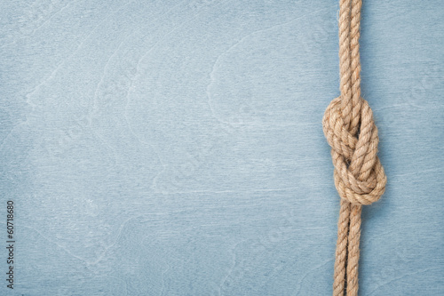 Fotobehang Oceanië Ship rope knot on wooden texture background