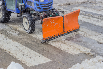 Tractor snowplow is cleaning the pedestrian crossing and sprinkl