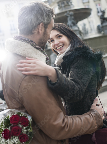 romantic guy  holding red roses behind his back for his girlfrie