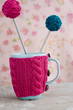 Blue cup in pink sweater  with ball of yarn
