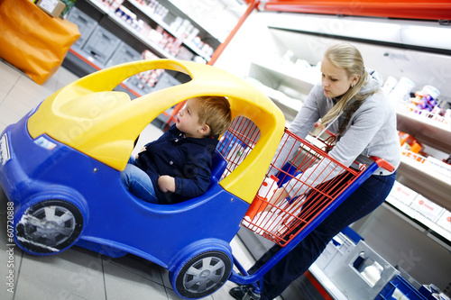 Young boy in a child friendly supermarket trolley