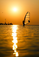 Silhouette of surfer at sunset passing by