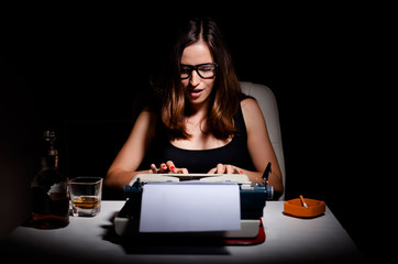 Novelist working on her book using typewriter