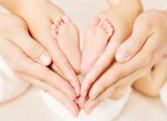 Newborn baby feet in parents hands. Love simbol as heart sign