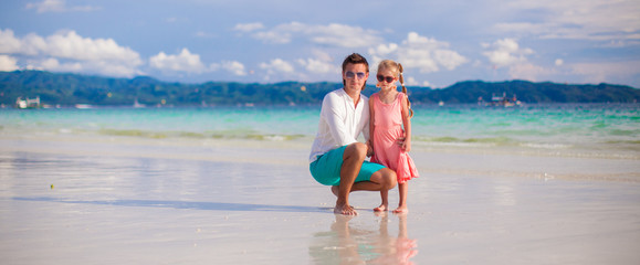 Adorable girl and young man on white sandy beach