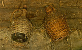 Wicker bottles hanging on a wall for a long time