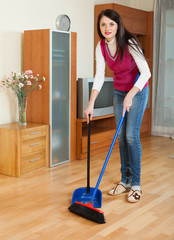 Brunette  girl with dustpan and brush