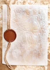 sheet of paper with a wax seal on old paper background
